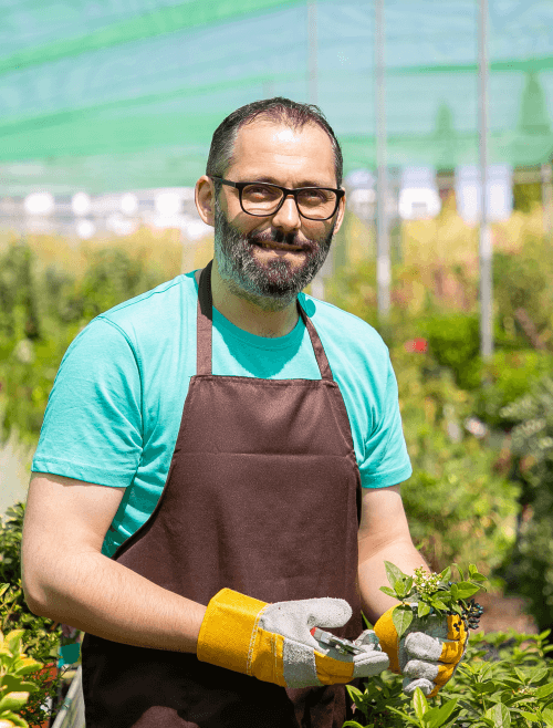 positive-male-florist-standing-among-rows-with-potted-plants-greenhouse-cutting-bush-holding-sprouts 1 (2) (1)