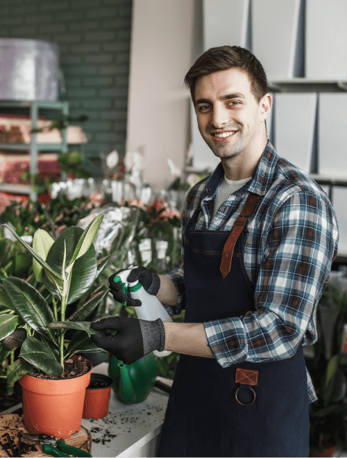 smiling-man-spraying-plants-garden-center (1)